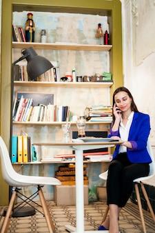 Mulher fala no telefone sentado no café