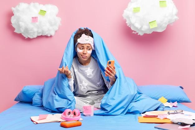 Mulher fala online com um amigo dando de ombros com hesitação, vestida com pijamas e poses de casa em uma cama confortável isolada em rosa