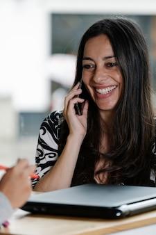 Mulher falando ao celular com uma cara sorridente