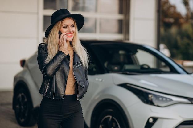 Mulher falando ao telefone ao lado do carro