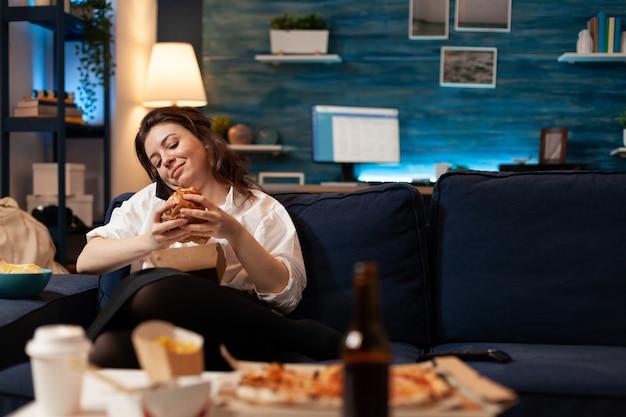 Mulher falando ao telefone com amigos, segurando um hambúrguer delicioso e saboroso nas mãos