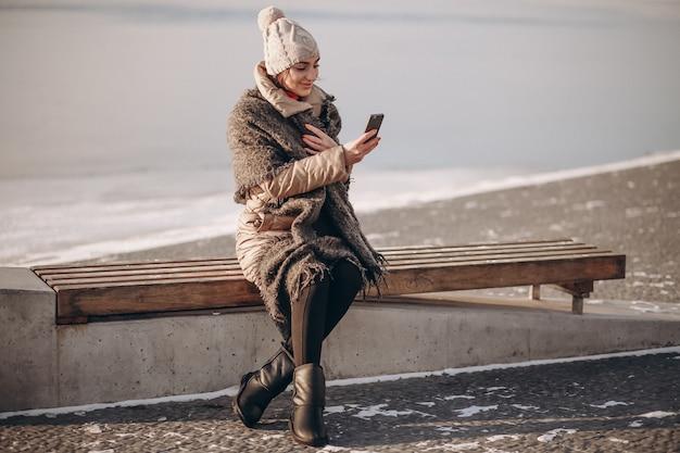 Mulher falando ao telefone e sentada em um banco junto ao lago