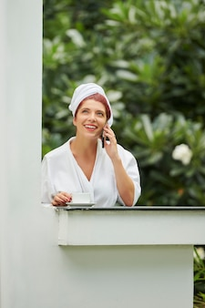 Mulher falando ao telefone e tomando café
