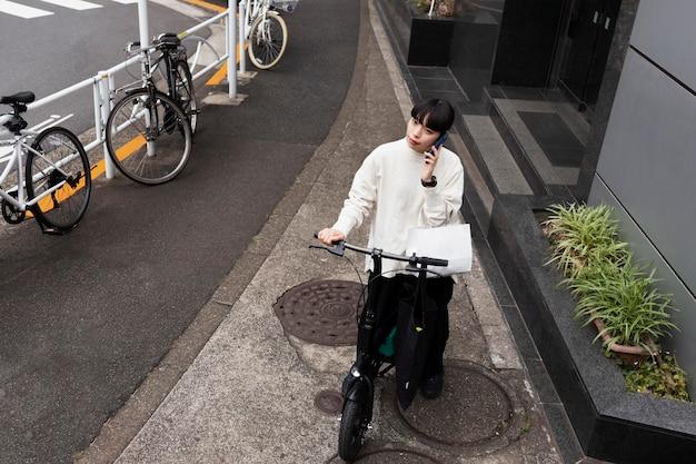 Mulher falando ao telefone e usando bicicleta elétrica na cidade