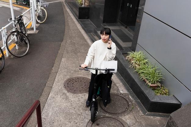 Mulher falando ao telefone e usando bicicleta elétrica na cidade Foto gratuita