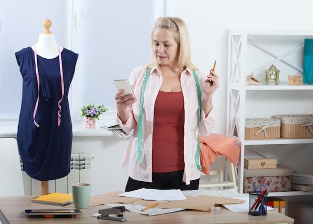 Mulher falando ao telefone em pé perto da mesa na oficina com roupas penduradas