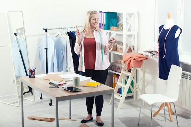 Mulher falando ao telefone em pé perto da mesa na oficina com roupas
