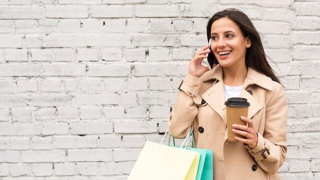 Mulher falando ao telefone enquanto toma café e segura sacolas de compras