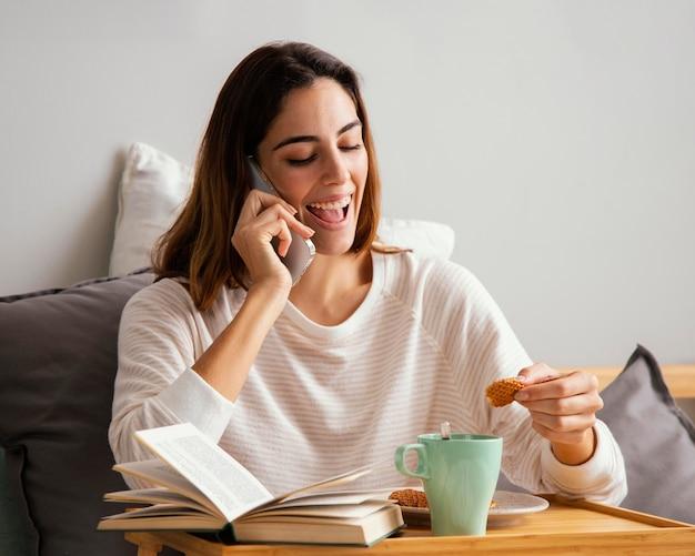 Mulher falando ao telefone enquanto toma o café da manhã em casa