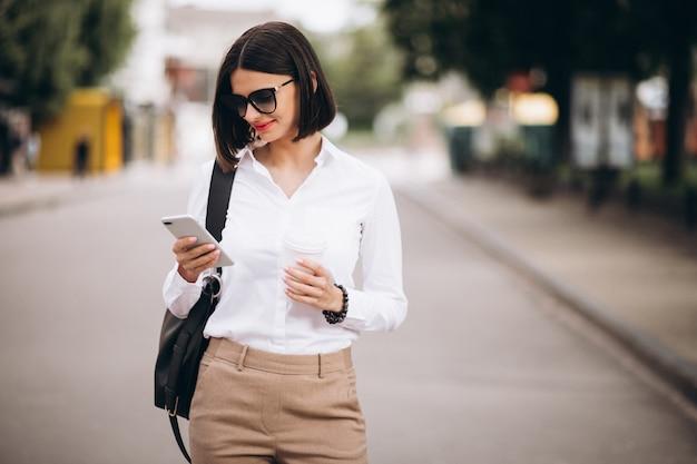 Mulher falando ao telefone fora das ruas da cidade