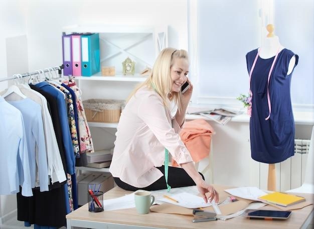 Mulher falando ao telefone na oficina com roupas
