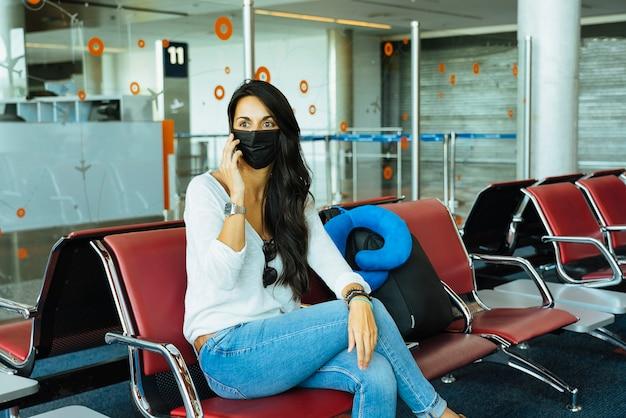 Mulher falando ao telefone no aeroporto com máscara protetora durante o coronavírus.