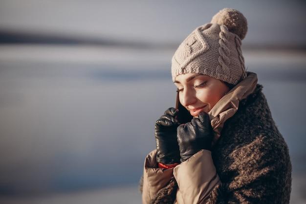 Mulher falando ao telefone no inverno pelo lago