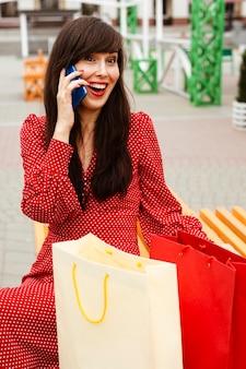 Mulher falando ao telefone sentada ao lado de sacolas de compras