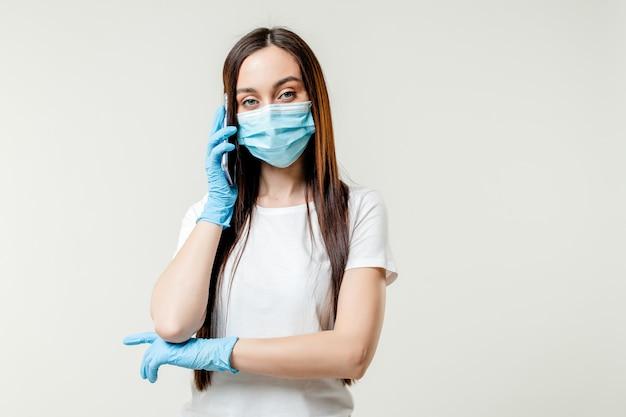 Mulher falando ao telefone usando luvas e máscara