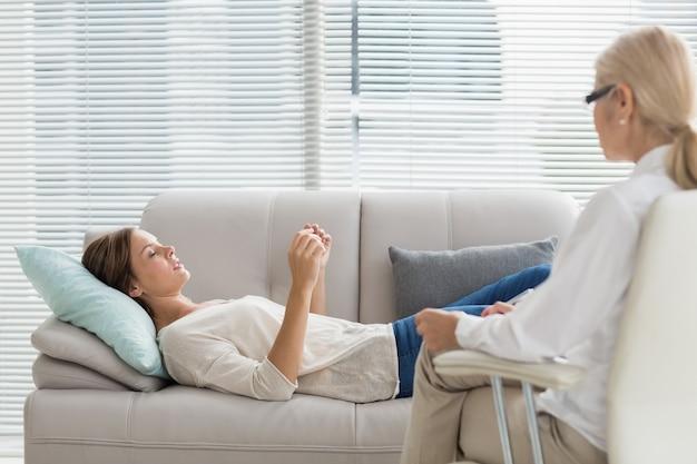 Mulher falando com o terapeuta enquanto estava deitado no sofá