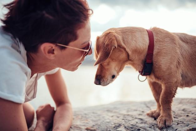 Mulher falando com seu cachorro na praia