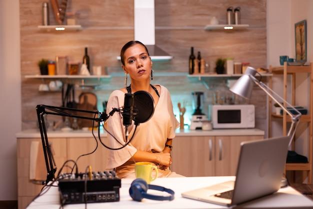 Mulher falando durante o programa online para um microfone profissional. programa on-line criativo produção no ar, transmissão pela internet, transmissão de conteúdo ao vivo, gravação de comunicação em mídia social digital