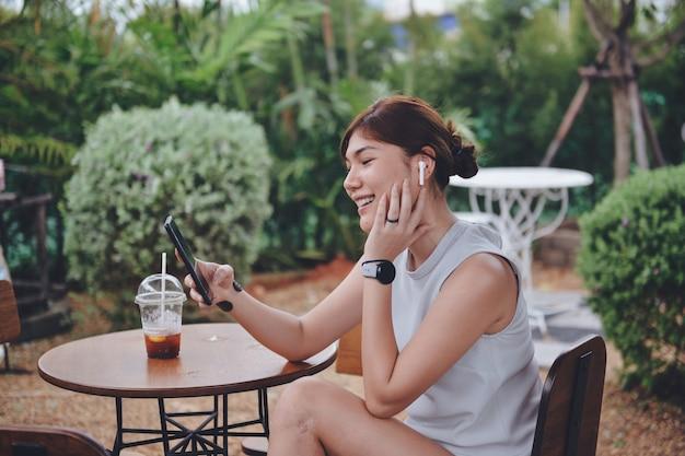 Mulher falando em bate-papo por vídeo via mobie digital e airpod branco sem fio enquanto está sentada