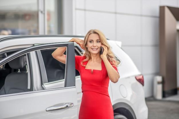 Mulher falando em smartphone perto do carro