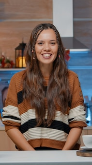 Mulher falando em videochamada na cozinha decorada de casa