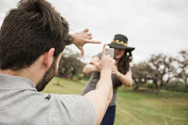Mulher falando foto de um homem fazendo quadro de mão no parque