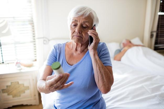 Mulher falando no celular e segurando um frasco de remédio no quarto em casa
