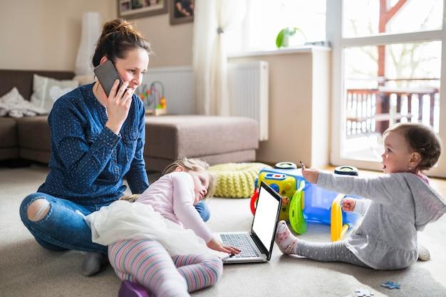 Mulher falando no celular enquanto a filha olhando para a tela do laptop