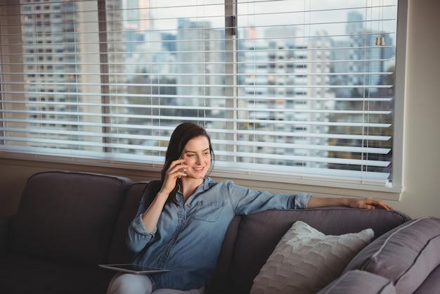 Mulher falando no celular enquanto está sentada no sofá