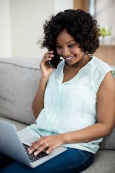 Mulher falando no celular enquanto estiver usando o laptop na sala de estar