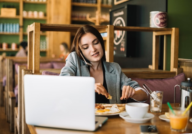 Mulher falando no celular enquanto tomando café da manhã no café