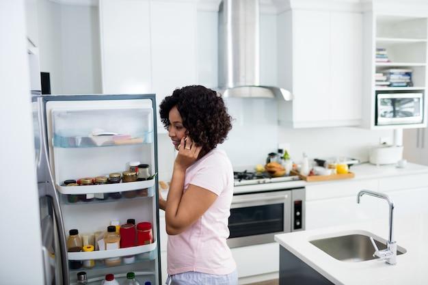 Mulher falando no celular na cozinha