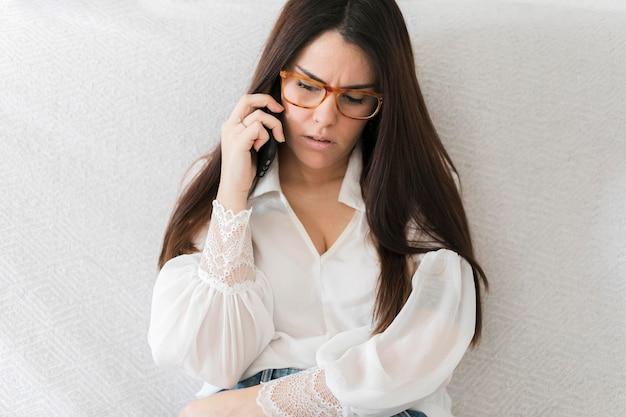 Mulher falando no telefone e concentrando-se