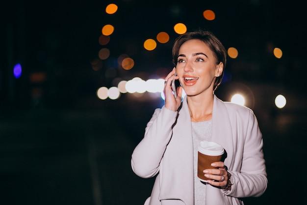 Mulher falando no telefone e tomando café lá fora na rua à noite