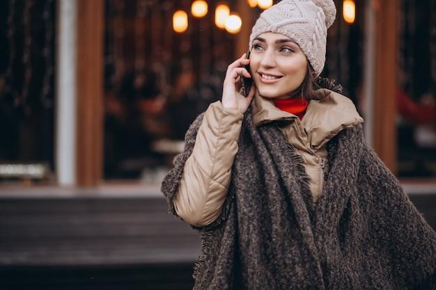 Mulher falando no telefone fora do bar no inverno