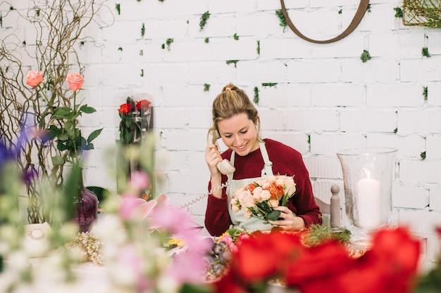 Mulher falando no telefone na loja floral