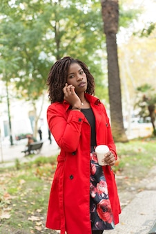 Mulher falando pelo smartphone e olhando