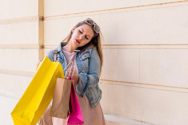 6fd6b724d Mulher falando por telefone e olhando para a sacola de compras