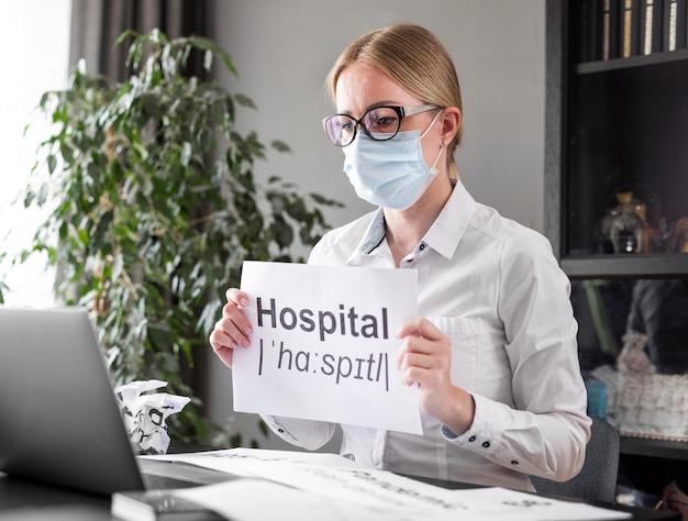Mulher falando sobre o hospital com seus alunos