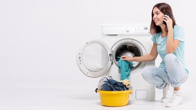 Mulher, falando, telefone, perto, lavadora roupa
