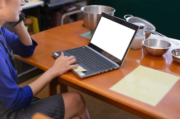 Mulher falar no celular e trabalhando no laptop com ingrediente de padaria na mesa.