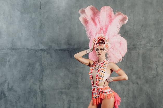 Mulher fantasiada de samba ou lambada com plumagem de plumas rosa.