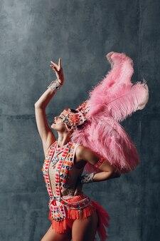 Mulher fantasiada de samba ou lambada com plumagem de plumas rosa