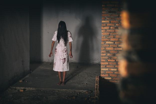Mulher fantasma assustadora, sombria em casa mal-assombrada, tema de halloween estende a mão e sangue