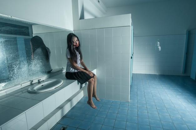 Mulher fantasma em uniforme de universidade tailandesa no banheiro