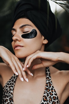 Mulher fascinante com tapa-olhos, posando no fundo da natureza. linda jovem de turbante preto, desfrutando de tratamento facial.