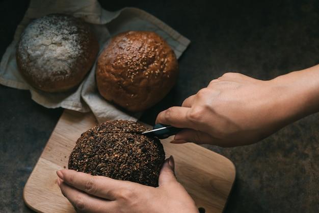 Mulher fatias de pão na mesa de madeira