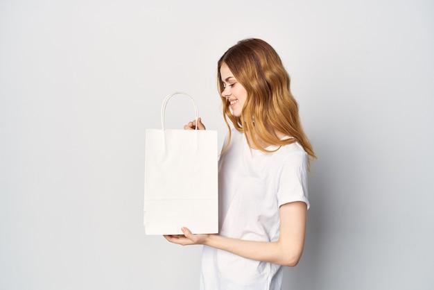 Mulher faz camisetas com pacote em compras de entretenimento de mãos