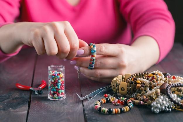 Mulher faz contas de artesanato