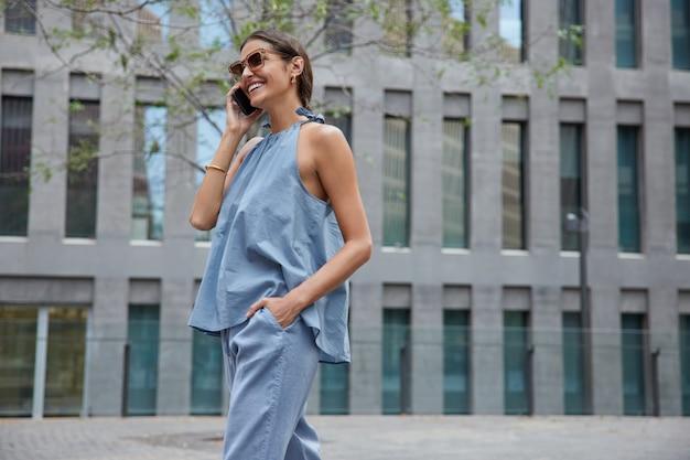 Mulher faz conversa internacional no smartphone, usa roupas da moda, óculos de sol gosta de fazer chamadas no celular, caminha ao ar livre perto de um prédio moderno